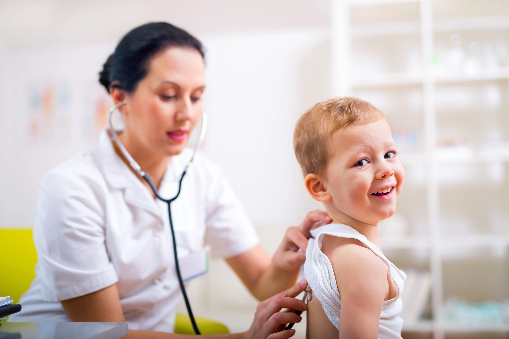 A nurse using a stethoscope on a child