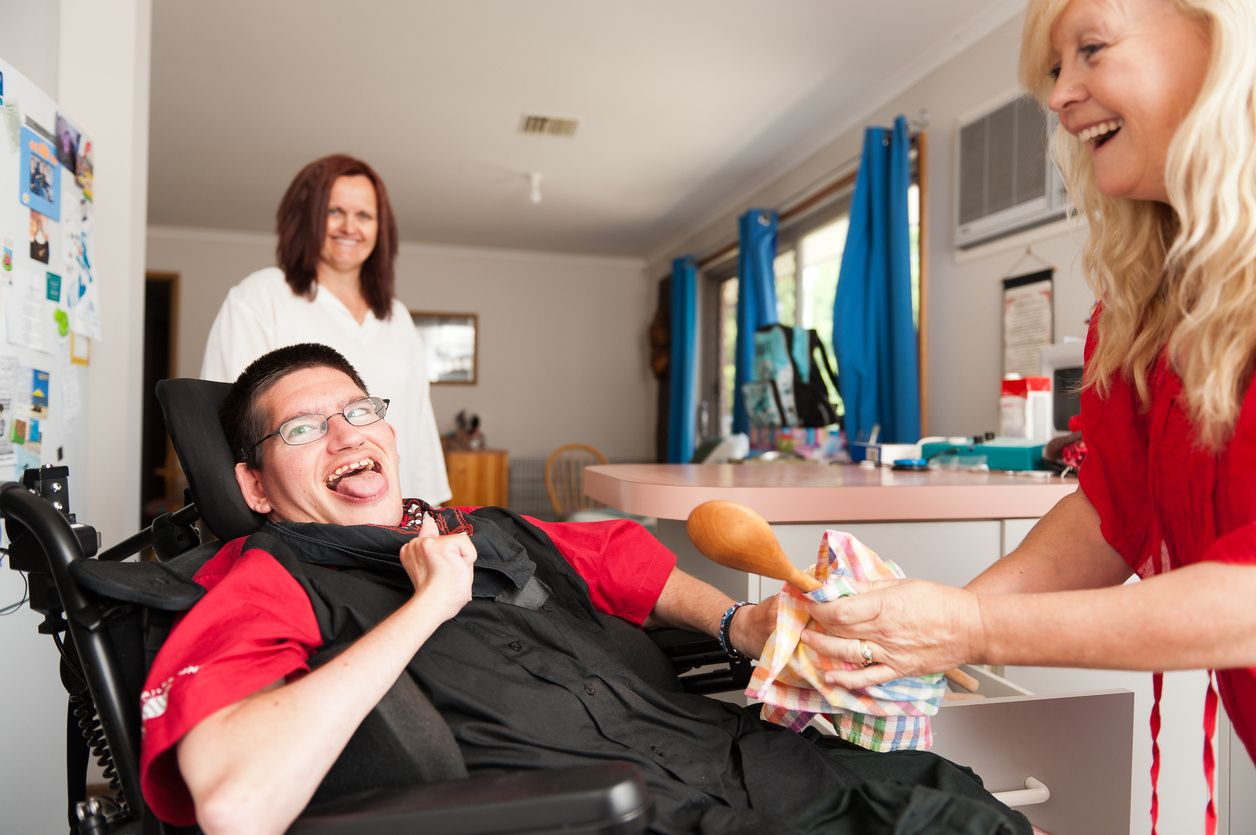 A person in red giving a wooden spoon to a patient